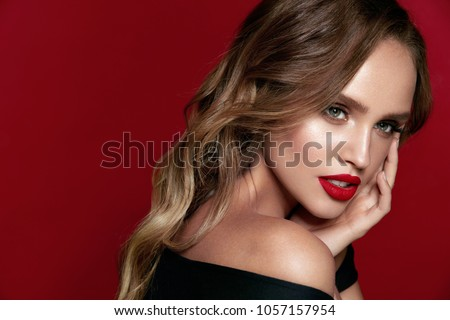 Beautiful Woman With Beauty Makeup On Face, Red Lipstick On Lips And Glamourous Look On Red Background. High Quality Image. #1057157954