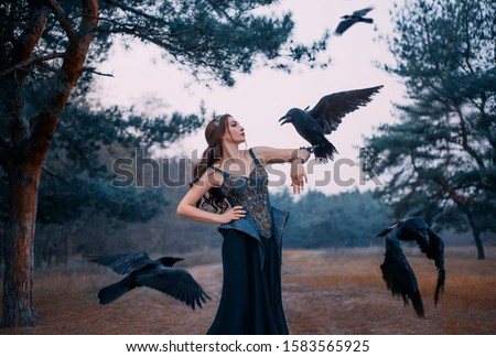 Beautiful woman with birds. Imperious strong power witch called her dark servants ravens. Queen in black dress medieval style. Leather corset embroidered metal gold, precious stones. Dusk cold forest