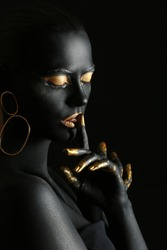 Beautiful woman with black and golden paint on her body against dark background