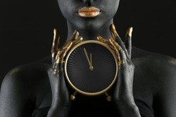 Beautiful woman with black and golden paint on her body holding clock against dark background, closeup
