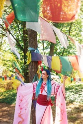 beautiful woman with blue dreadlocks and pink japanese costume holding colorful flags, asian festival, oriental fashion