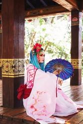 beautiful woman with blue dreadlocks and pink japanese costume, sitting on the floor with umbrella, asian festival, oriental fashion