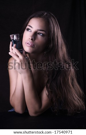 beautiful woman with bottle of perfume - stock photo