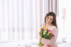 Beautiful woman with bouquet of tulips on bed at home