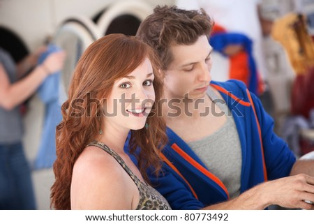 Beautiful woman with boyfriend smiles in the laundromat