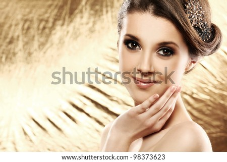 Beautiful woman with brooch in hair over golden background