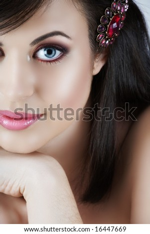 Beautiful woman with brown hair and pink make-up looking at camera
