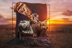 Beautiful woman with bull in sunset