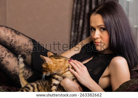 Beautiful woman with cat portrait. Brunette with bengal cat close-up.