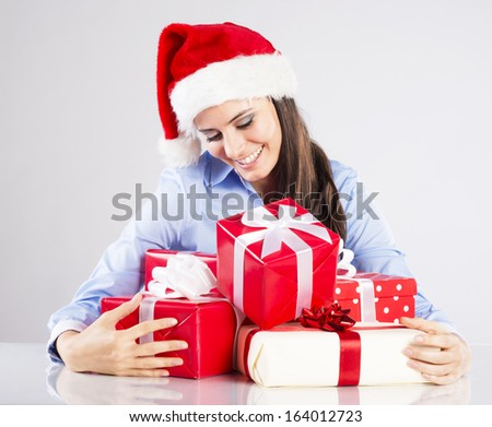Beautiful woman with christmas hat has gifts on desk in her office