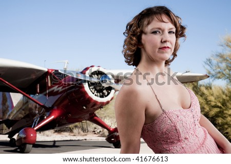 Beautiful woman with classic 1930's private plane