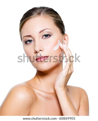 Beautiful woman with clean skin applying cosmetic cream on face