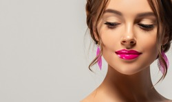 Beautiful woman with clean skin on her face. Beauty, cosmetics and cosmetology. Fashion earrings as accessories. Cosmetics and makeup, fuchsia lips.