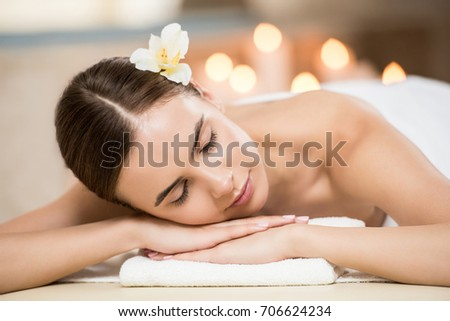 Beautiful woman with closed eyes relaxing in spa salon