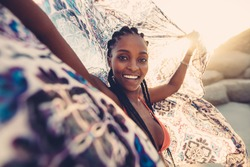 Beautiful woman with cloth in the breeze of a summer day. African young female on beach with a scarf looking at camera and smiling.