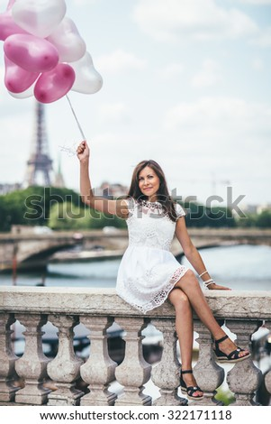 Beautiful woman with colorful balloons in front of the Eiffel tower in Paris, selective focus, France