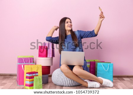 Beautiful woman with credit card and laptop indoors. Online shopping concept