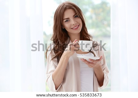 Shutterstock Beautiful woman with cup of aromatic coffee standing near window