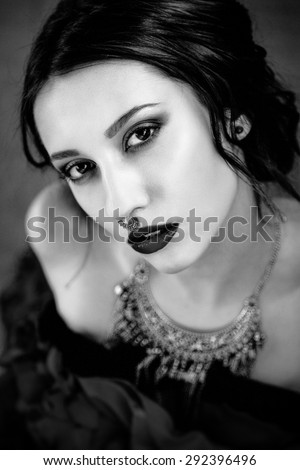 Beautiful woman with cute face bright make up red lips and piercing on nose black and white photo
