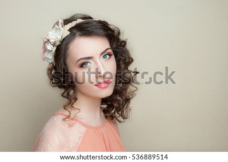 Beautiful woman with dark curly hair and fashion make up, fair background