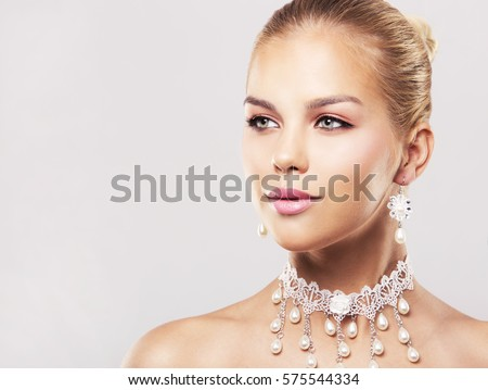 Shutterstock beautiful woman with dark makeup and pink lipstick posing on light background wearing bridal spring and summer jewellry necklace