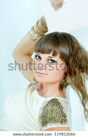 Beautiful woman with evening make-up. Jewelry and Beauty. Fashion photo. Sitting and looking to the side.