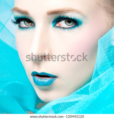 beautiful woman with extreme colorfull make up in turquoise portrait