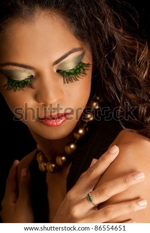 Beautiful woman with eyelashes made up of bird feathers
