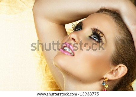 beautiful woman with fantasy golden eye make-up and good skin texture and pore definition