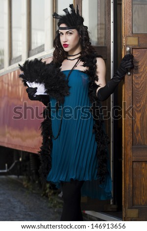 beautiful woman with feather dusters and fan stands in front of the tram, 1930s
