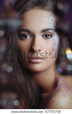 beautiful woman with festive makeup in color spray and boke lights