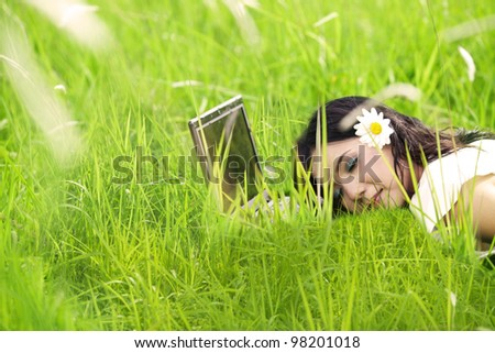 Beautiful woman with flower enjoys spring sleeping on laptop outdoor