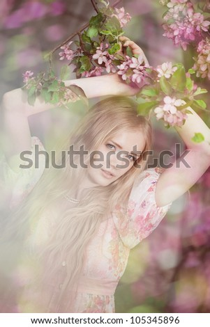Beautiful woman with flowering tree - stock photo