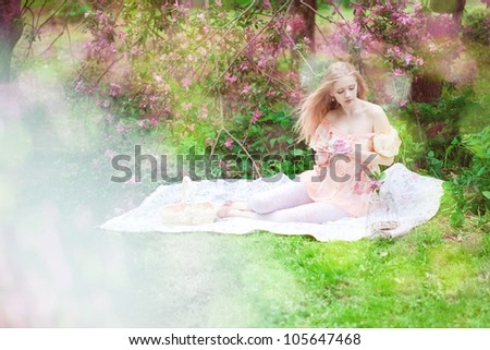 Beautiful woman with flowering tree drinking tea