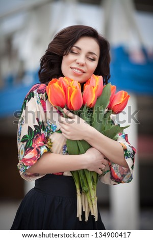 Beautiful woman with flowers bouquet in spring park outdoors. Romantic sexy girl with tulips flowers for anniversary or Valentines. happy smiling woman with bouquet. brunette woman on dating summer