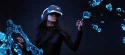 Beautiful woman with flowing hair over dark magic background. Girl in glasses of virtual reality while touching air in blue neon lights. Augmented reality, game, future technology concept. VR.