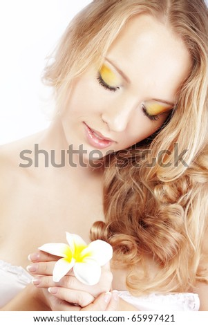 Beautiful woman with frangipani flower in her hair