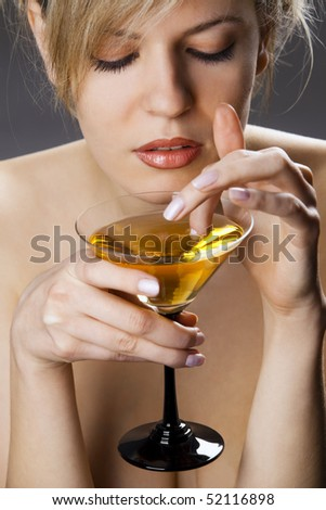 Beautiful woman with glass of cocktail going wool-gathering