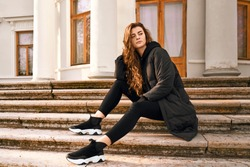 Beautiful woman with green eyes, long curly dark hair is wearing black jacket, sweater, jeans, sneakers, sitting on steps of stairs, staring away, has long legs. Thoughtful girl holds hand on head.