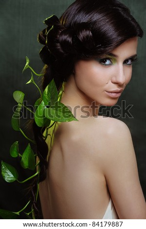 Beautiful woman with green make up and some leaf in her hair - stock photo