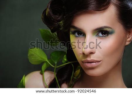 Beautiful woman with green make up and some leaf in her hair