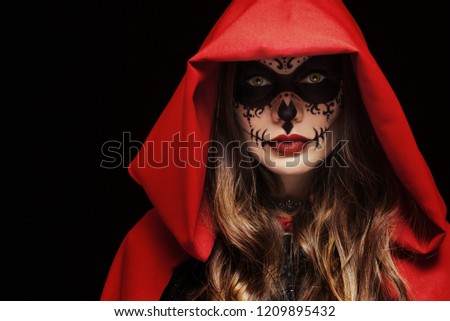 Stock Photo Beautiful woman with Halloween sugar skull face art, makeup, wearing wearing red cape, hood, looking at camera. Close up studio portrait. Dark, black background. Copy, empty space for text