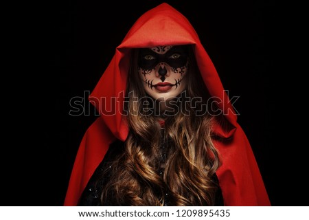 Stock Photo Beautiful woman with Halloween sugar skull face art, makeup, wearing wearing red cape, hood, looking at camera. Studio portrait. Dark, black background. Copy, empty space for text