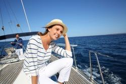 Beautiful woman with hat enjoying cruising on boat