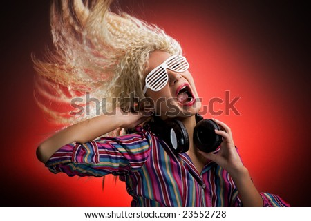 Beautiful woman with headphones dancing and screaming