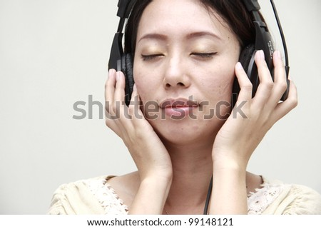 Beautiful woman with headphones, listening to music
