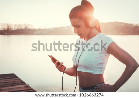 Beautiful woman with headphones listening to music while workout outdoors #1026663274