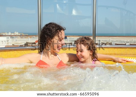 beautiful woman with her daughter both smiling in hot tub on cruise ship.
