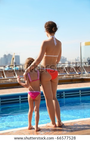 beautiful woman with her daughter standing near swimming pool.