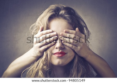 Beautiful woman with her eyes covered by someone else's hands